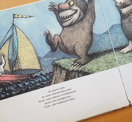 """Photo d'une page de l'album """"Max et les Maximonstres"""" : Max part en bateau et les Maximonstres se lamentent depuis la rive. Texte : """"Ne partez pas, ne nous abandonnez pas ! Nous vous aimons terriblement, nous vous mangerons !  Non, dit seulement Max."""